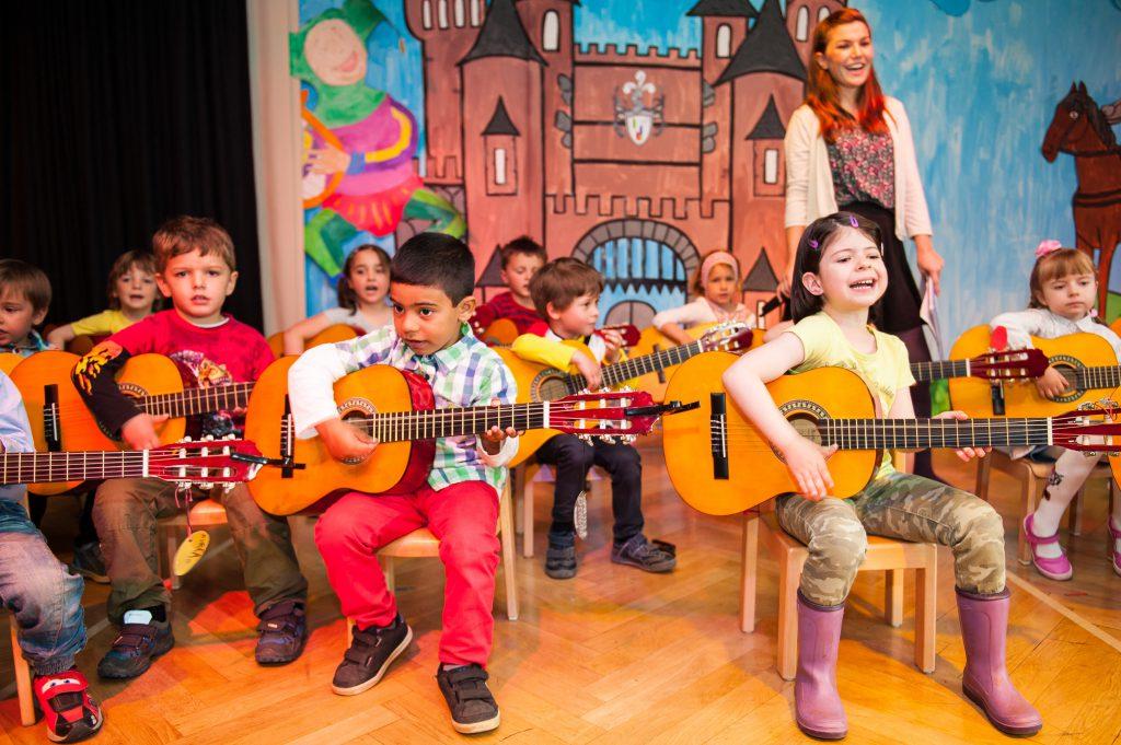 Kinder (hier bei einem Musikprojekt mehrerer Kitas in Düsseldorf) musizieren ab 4 Jahren auf der C-Gitarre (Foto von Uwe Reinert)