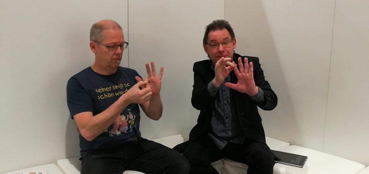 Matthias Meyer-Göllner und Wolfgang Hering üben Fingerspiele auf der Didacta 2018